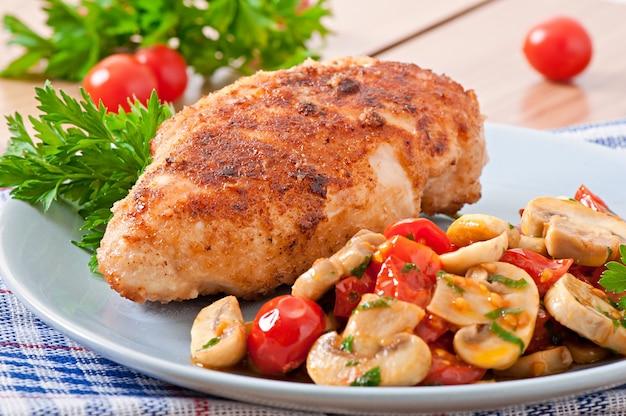 Kipfilet in krokant paneermeel gegarneerd met champignons en tomaten