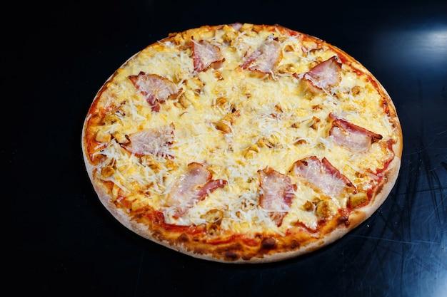 Kipfilet met romige saus en geraspte kaas op een pizza. lekkere verse pizza op een dikke bodem met vlees
