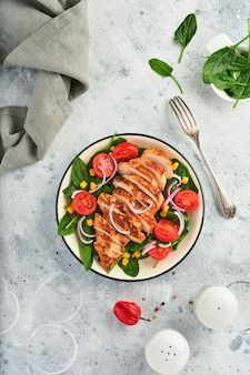 Kipfilet met salade spinazie, kerstomaatjes, korenbloem en ui. gezond eten. keto-dieet, dieetlunchconcept. bovenaanzicht op witte achtergrond.