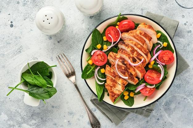 Kipfilet met salade spinazie, kerstomaatjes, korenbloem en ui. gezond eten. keto-dieet, dieetlunchconcept. bovenaanzicht op witte ondergrond.