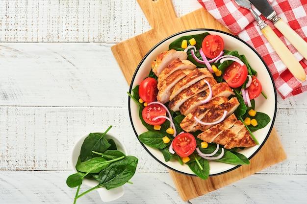 Kipfilet met salade, spinazie, kerstomaatjes, korenbloem en ui