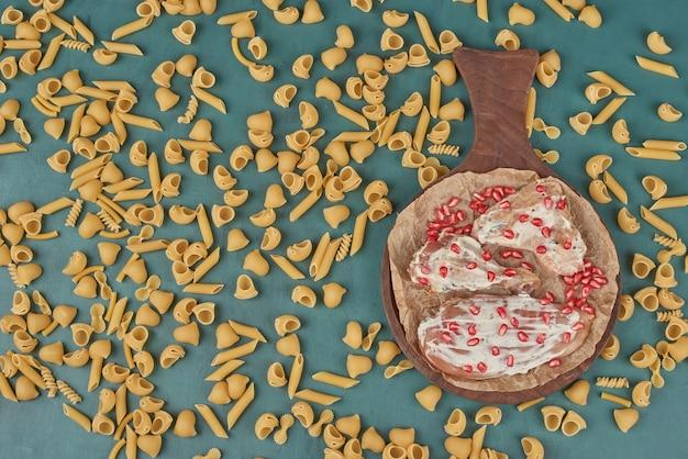 Kipfilet op een houten bord met kruiden en pasta.
