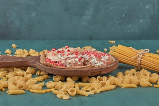 Kipfilet op een houten bord met rond pasta.