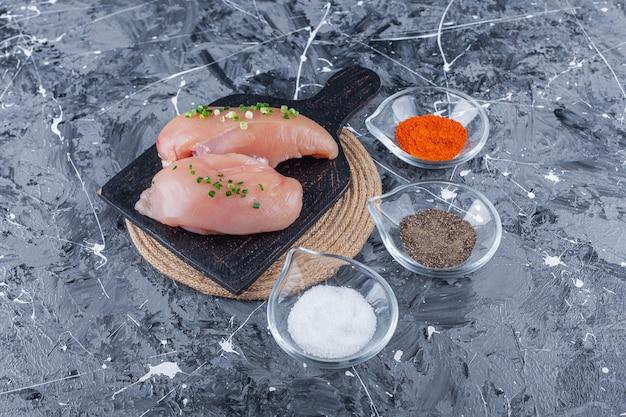 Kipfilet op een snijplank op een onderzetter naast kommen vol kruiden, op de blauwe tafel.