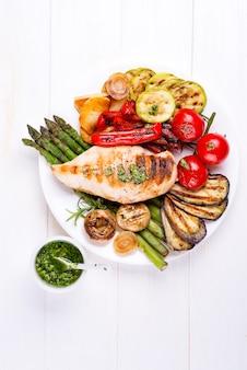 Kipfiletgrill met bbq-groenten en pestosaus in een plaat op hout