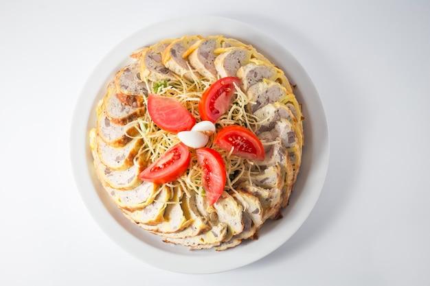 Kipgehakt met pasta, tomaten en riet eieren op het bord.
