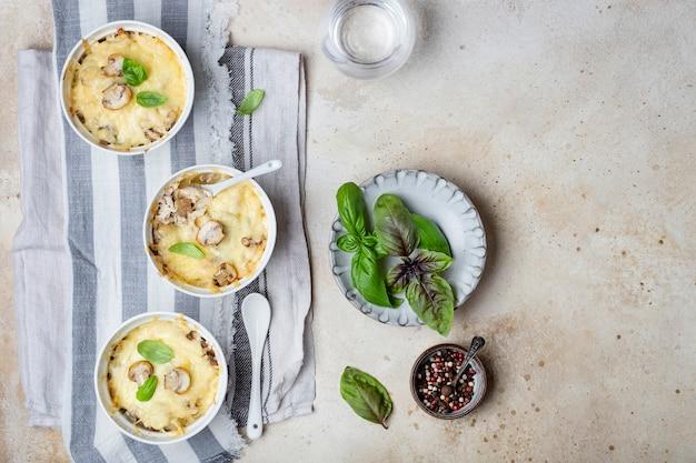 Kipjulienne en champignons in portievorm op een lichte ondergrond