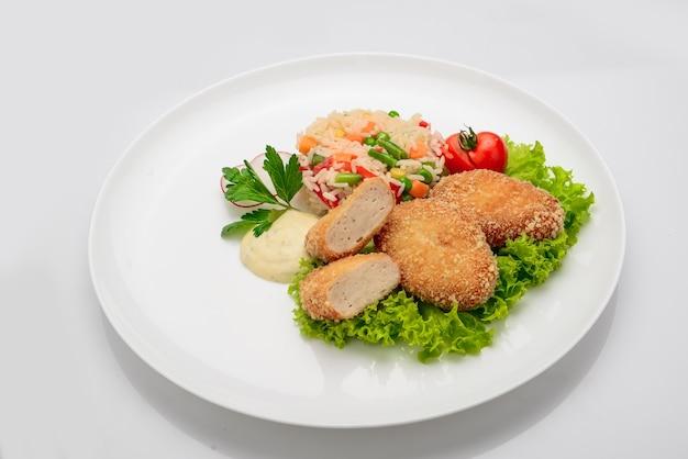 Kipkoteletten in beslag met risotto en groenten. witte achtergrond.