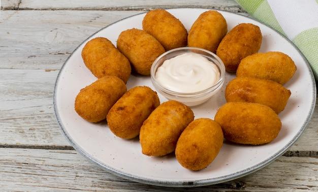 Kipkroketten met mayonaisesaus geserveerd op een bord