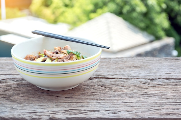 Kipnoedels in een keramische beker op een houten tafel.