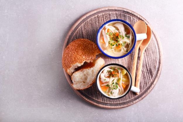 Kipnoedelsoep geserveerd in mokken met broodje