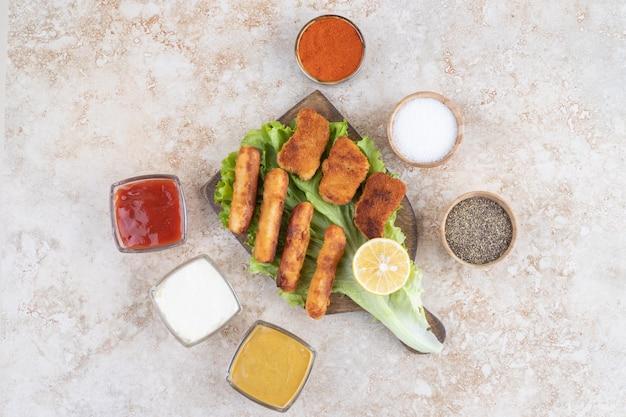 Kipnuggets en gebakken worstjes op een groen slablad op een houten bord.