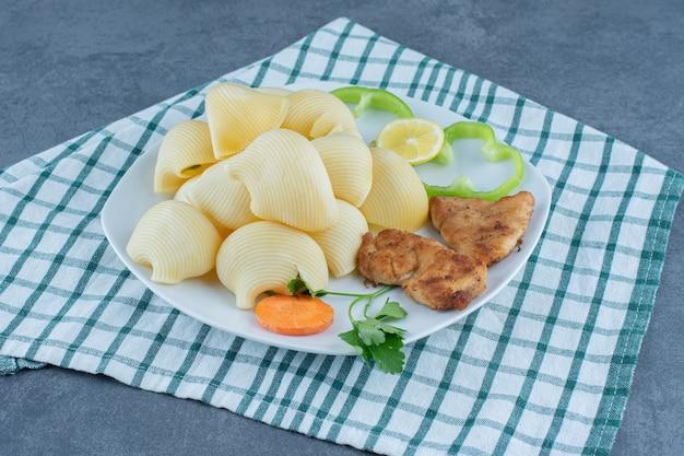 Kipnuggets en gekookte pasta op witte plaat.