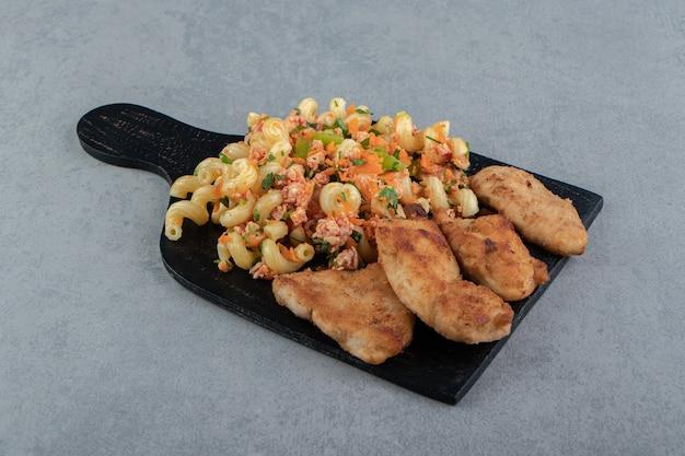 Kipnuggets en gekruide pasta op een houten bord.