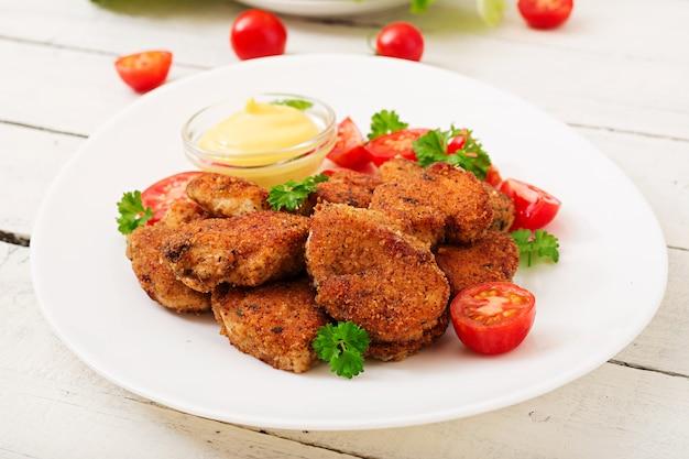 Kipnuggets en saus in plaat op een witte houten tafel
