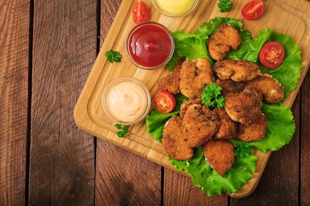 Kipnuggets en saus op een houten tafel