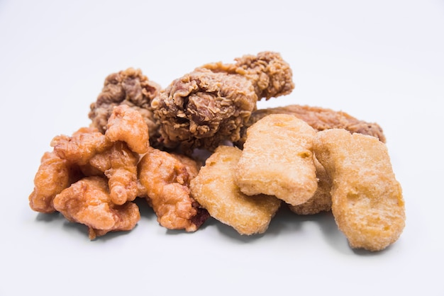 Kipnuggets; gebraden kippentrommelstok en knapperige kippenpopcorn die op witte achtergrond wordt geïsoleerd