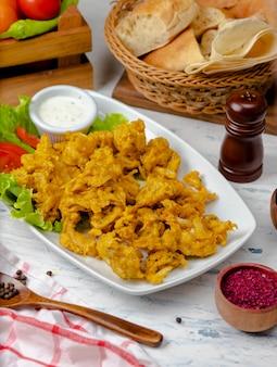 Kipnuggets geserveerd met mayonaise-yoghurtsaus in witte plaat met sla en tomaten
