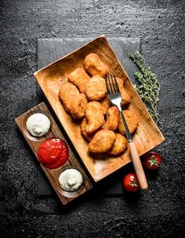 Kipnuggets in een plaat met vork, tijm en verschillende sauzen op rustieke tafel