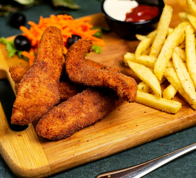 Kipnuggets kfc-stijl met frites, mayonaise, ketchup en groentesalade