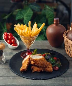 Kipnuggets met franse frietjes op zwarte stenen bord