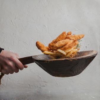 Kipnuggets met frietjes en menselijke hand in vlieg