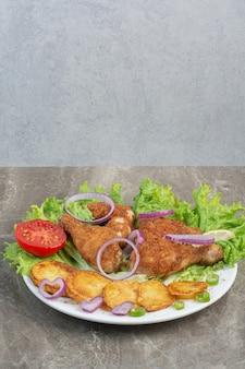 Kipnuggets met gebakken aardappel en ui op een witte plaat.