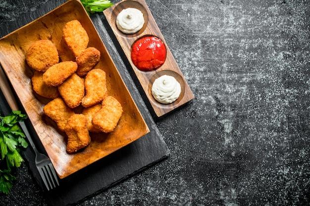 Kipnuggets met peterselie en verschillende sauzen op donkere rustieke tafel