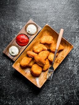 Kipnuggets met verschillende sauzen op donkere rustieke tafel