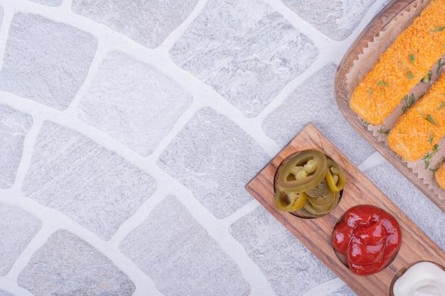 Kipnuggets met verschillende sauzen op een houten bord