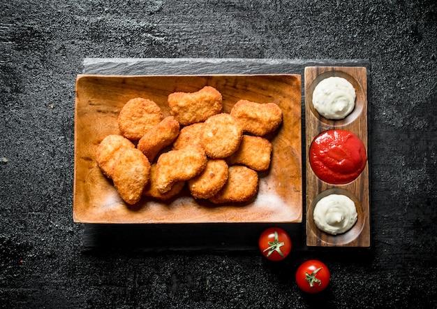 Kipnuggets met verschillende sauzen op zwarte rustieke tafel