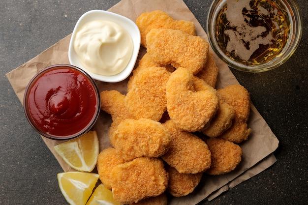 Kipnuggets met witte en rode saus en bier en citroen op een bruine achtergrond. fastfoodclose-up. uitzicht van boven