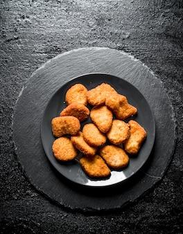 Kipnuggets op de plaat op zwarte rustieke tafel.