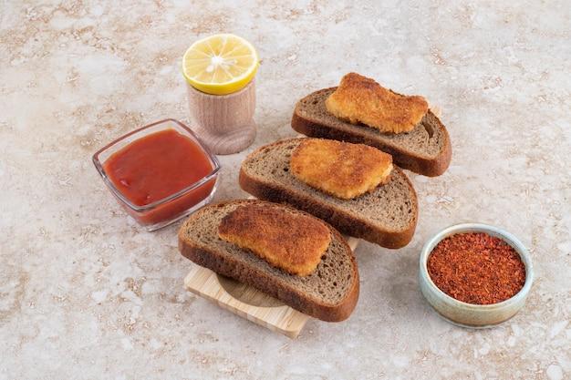 Kipnuggets op een houten bord met sauzen opzij.