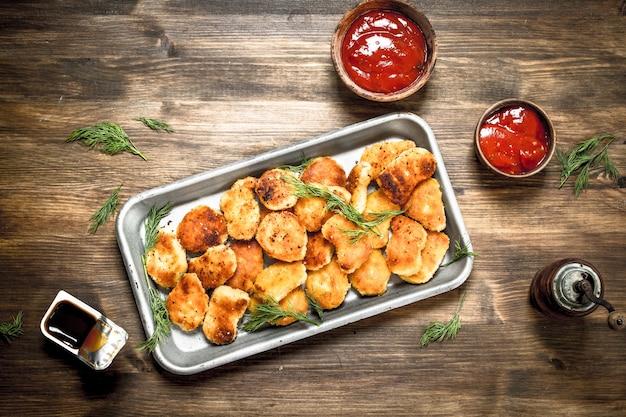 Kipnuggets op een stalen bakje met saus. op een houten tafel.