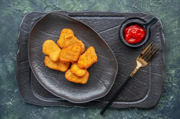 Kipnuggets op een zwarte plaat en vorkketchup op een donkere kleurschaal op een donkere ondergrond