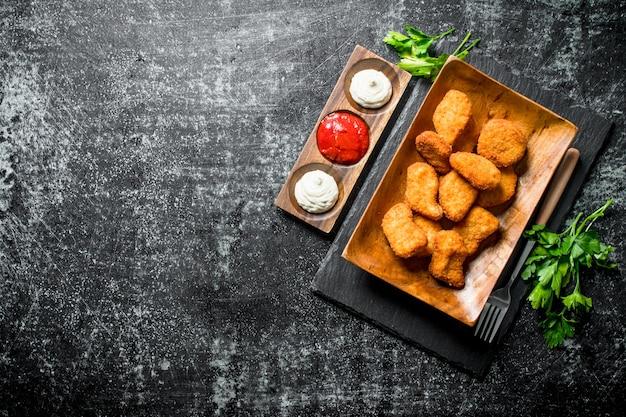 Kipnuggets op plaat met greens en verschillende sauzen op donkere rustieke tafel