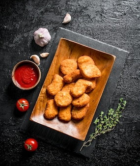Kipnuggets op plaat met saus, tijm en knoflook op zwarte rustieke tafel