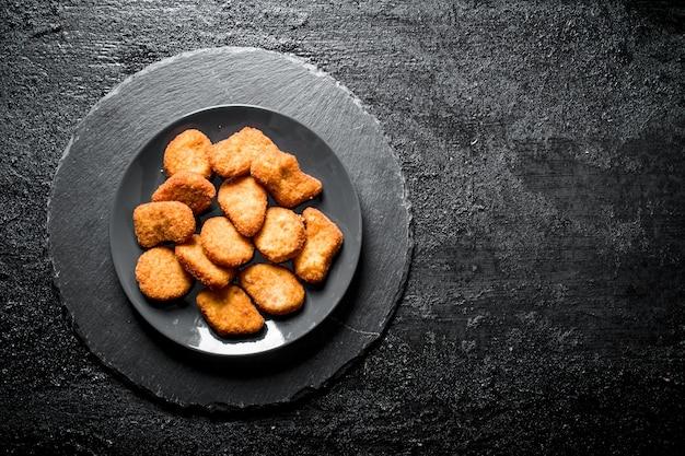 Kipnuggets op plaat op zwarte rustieke tafel