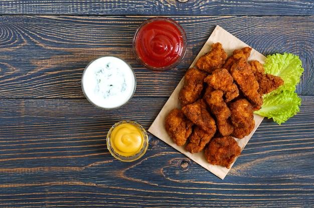 Kipnuggets. stukken gefrituurd krokant vlees, op papier met verschillende sauzen op een houten tafel. traditionele snack.