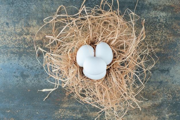 Kippen verse witte eieren die in hooi op marmeren achtergrond liggen
