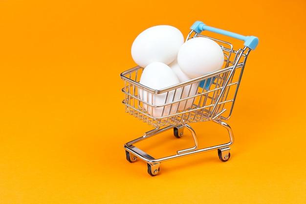 Kippen witte eieren in een boodschappenwagentje op sinaasappel