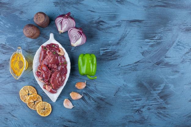 Kippenafval op een schaal, oliekom, zout, ui, knoflook en peper, op de blauwe achtergrond.