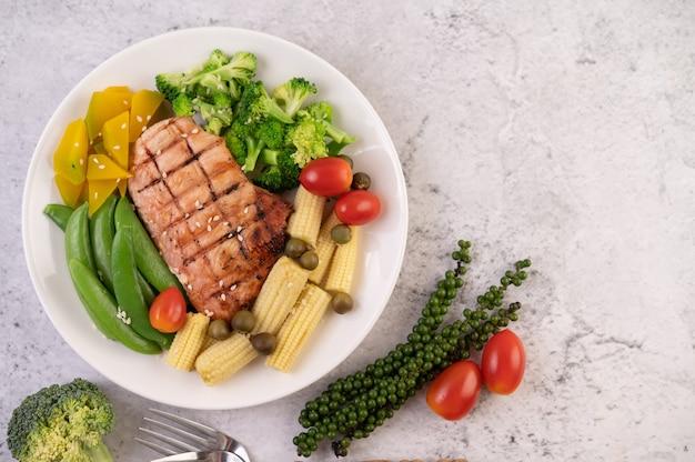 Kippenbiefstuk gegarneerd met witte sesam, erwten, tomaten, broccoli en pompoen in een witte plaat.