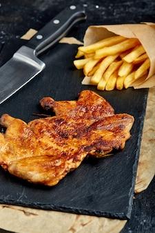 Kippenbiefstuk met frietjes op een zwarte ruimte
