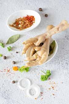 Kippenbotten, groenten, specerijen en kruiden voor bouillon op grijs