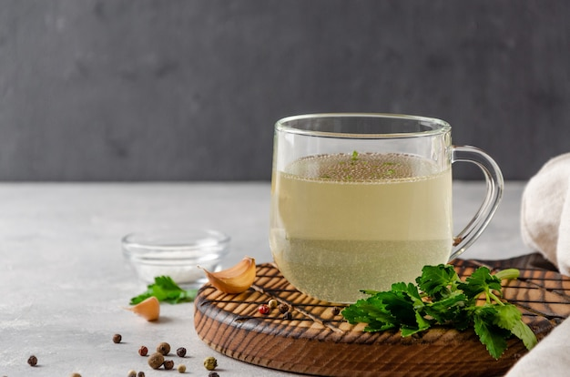 Kippenbouillon in een glazen beker met peterselie, knoflook en andere kruiden op houten dienblad op grijze achtergrond
