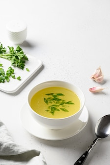 Kippenbouillon met groenen in witte kom over witte tafel. kopieer ruimte.
