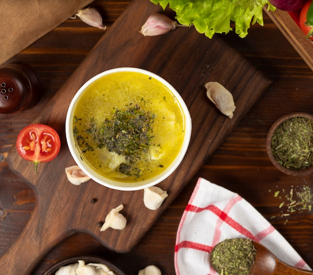 Kippenbouillon met kruiden soep in wegwerpbeker kom geserveerd met groene groenten.