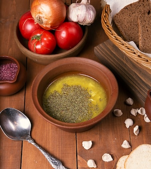 Kippenbouillon soep met kruiden en groenten. geserveerd in aardewerkkom met sumakh.